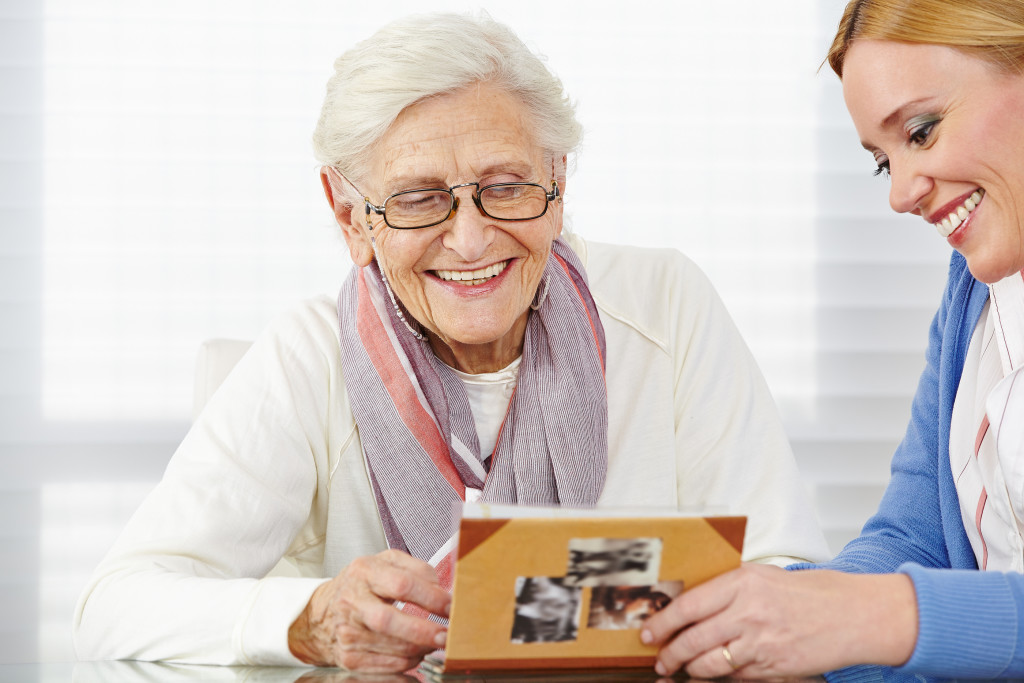 Happy senior woman watching photo album with eldercare nurse